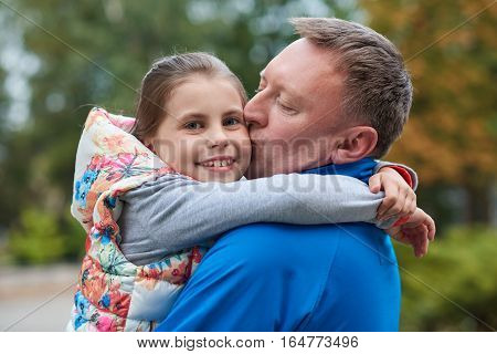Portrait of a father kissing his smiling little daughter while enjoying a day outside together in a park in the autumn