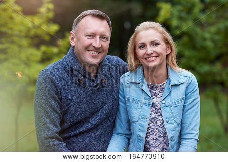 Portrait of a smiling mature couple sitting contently together on a bench in a park in the autumn