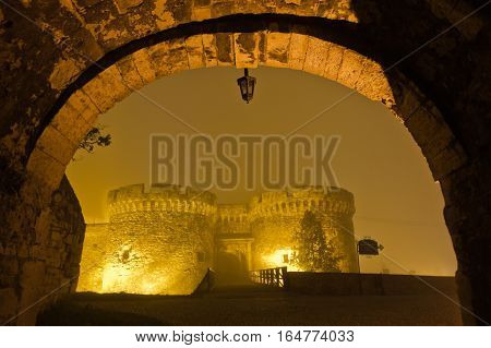 Bridge and towers of Kalemegdan fortress covered with fog at night, Belgrade, Serbia