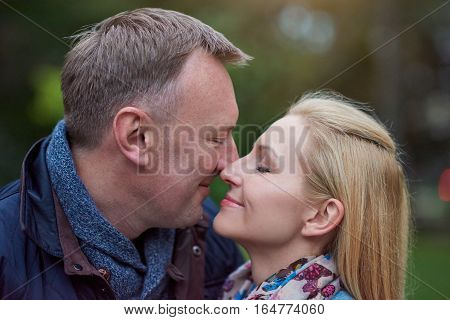 Smiling mature couple with their eyes closed about to kiss each other while standing together in a park in the autumn