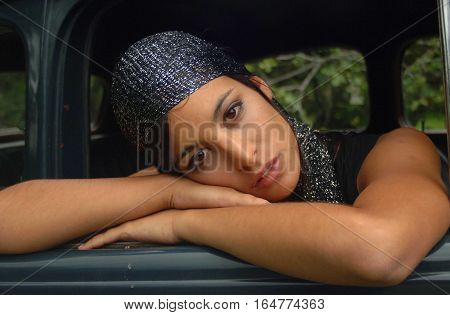 Gorgeous gypsy girl lying in the car door