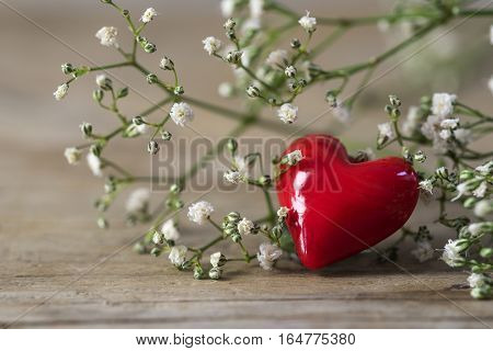 Red heart from glass and small white flowers on rustic gray wood love concept for mother's day and valentine's day close up selected soft focus very narrow depth of field