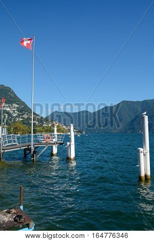 Swiss flag on the lake of Lugano in Tessin Switzerland