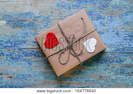 Gift box with hearts on wooden background with crackling effect. Valentine's Day Concept