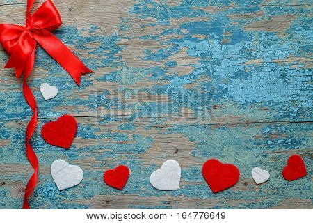 Red ribbon and hearts on wooden background with crackling effect. Valentine's Day Concept