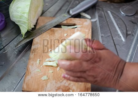 Senior women hands cutting cabbage for salad. cooking and home concept