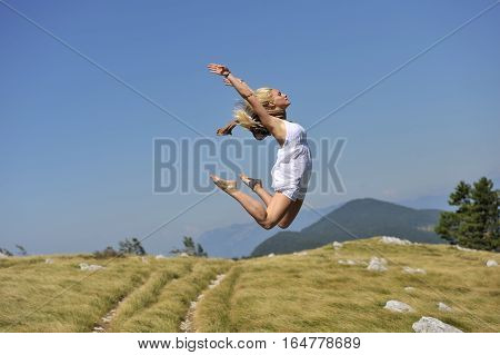 Freedom. Beautiful woman with light hair and in white dress jumping in nature. She is satisfied with her life. she was jumping on trampoline