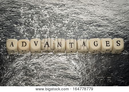 Advantages Word On A Wooden Cubes On A Shiny Silver Foil Background