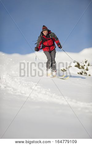 Man is skiing in deep snow out of ski run in pure nature