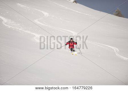 Skillful skier skiing downhill in deep snow, doing nice winding