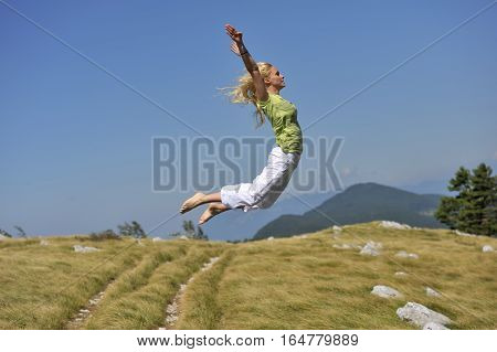 Vitality.  Happy and vital woman jumping in nature she was jumping on trampoline