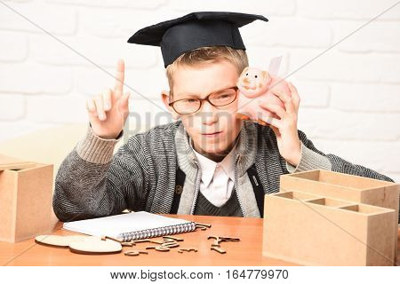 young cute pupil boy in grey sweater and glasses sitting at desk with copybook wooden numbers pink piggy pig bank in graduation cap with raised finger in classroom on white brick wall background