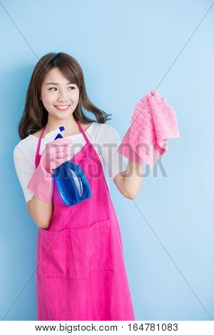 beauty housewife take rag and detergent isolated on blue background asian