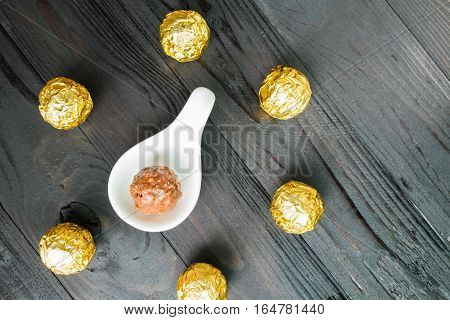 Chocolate ball wrapped in foil Chocolate ball on spoon chocolate background