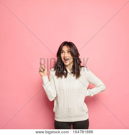 Excited young woman pointing her finger upward to copy space isolated over pink color background. Girl wearing warm sweater gesturing up to empty space