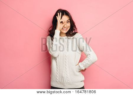 Young cheerful girl showing zero gesture with her fingers over pink color background. Discount and free concept.