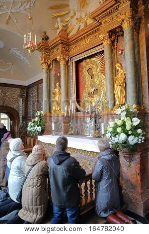 VILNIUS, LITHUANIA - DECEMBER 28, 2016: People praying in front of the icon of Our Lady of the Gates of Dawn in the Chapel of the Gates of Dawn