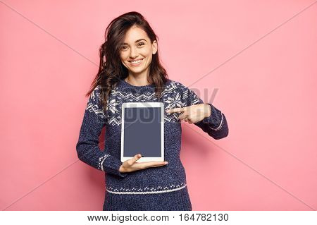 christmas, x-mas concept. smiling woman in winter clothes pointing her finger to empty tablet black screen.