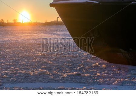 Icebreaker in the river ice on winter sunset. Nose of ship