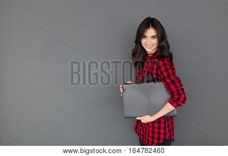 Happy young brunette woman in casual shirt smiling and holding a laptop on gray background with copy space.