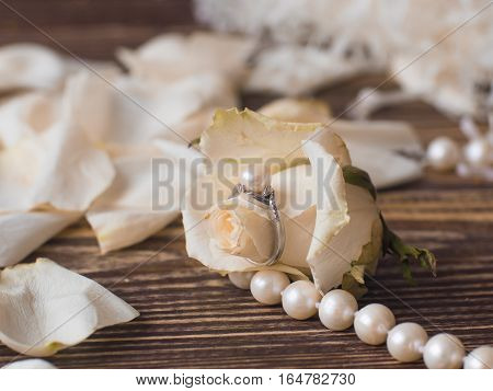 pearl necklace and ring with white flowers on woden background, macro
