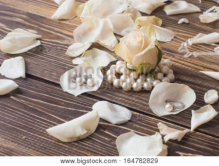 pearl necklace with white flowers on woden background, macro.