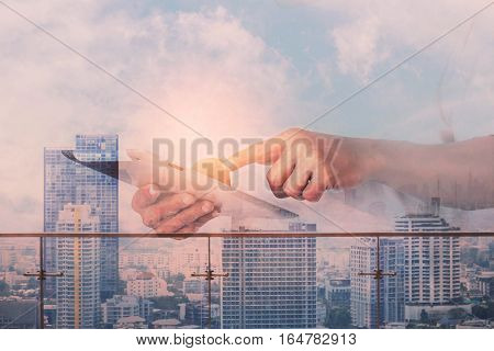 Hand holding tablets and city of business.