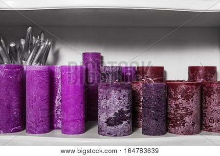Purple cylindrical candles on white shelf. home decor