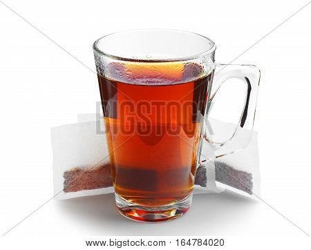 Transparent glass cup of tea and tea bags on white
