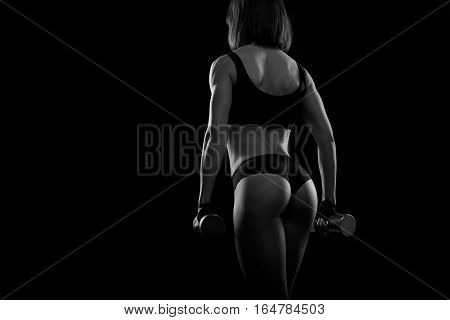 Strength is beautiful. Cropped black and white shot of a female bodybuilder with stunning strong muscular body posing with dumbbells
