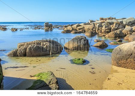 The little cave of Oudekraal Beach with calm, turquoise waters, white sand and large boulders, part of Table Mountain area in Cape Town, South Africa. This area is popular for diving and snorkeling.