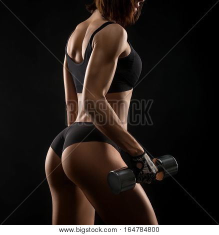 No extra fat. Closeup shot of a gorgeous young fitness female in sports bra and shorts exercising with dumbbells showing off her perfect muscular body