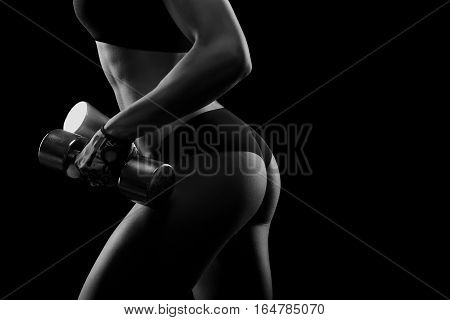 No way back. Black and white closeup shot of a perfectly shaped flawless backside of a young sportswoman with dumbbells in her hands