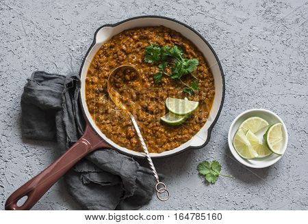 Cream coconut lentil curry in a cast iron skillet top view. Healthy vegetarian food