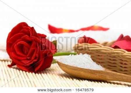 Spa essentials (bath salt in a spoon and rose petals)