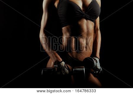 Keep on. Cropped closeup of wet perfect abs of a stunning witness woman with weights in her hands on black background