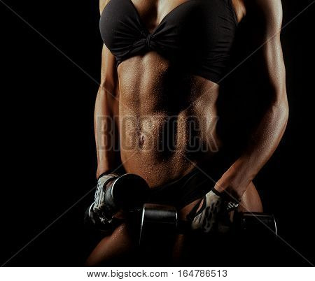 Perfect form. Closeup shot of a fitness woman with her perfect toned abs wet from a workout on black background