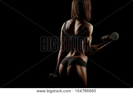 Killing the fat. Horizontal rearview studio shot of a gorgeous athletic woman exercising with dumbbells against black background copyspace