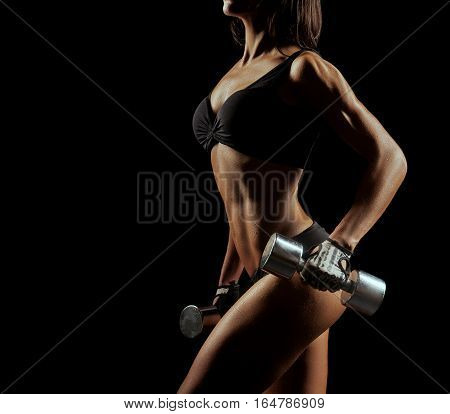 Strong mind in strong body. Cropped closeup of a fit young woman with perfectly shaped body exercising with weights on dark background copyspace