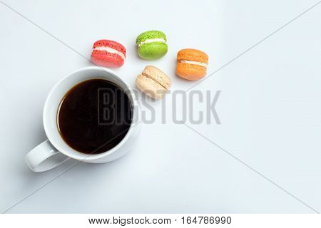 Sweet and colourful macaroons with cup of coffee on white background. Traditional french dessert. Top view, flat lay, space for text.