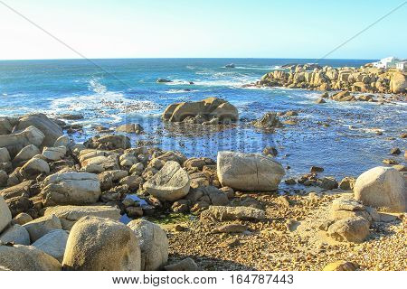 Coastal landscape with rocky beach and blue sky in Atlantic Ocean. Cape Town, Western Cape, South Africa.