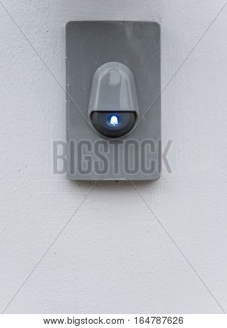 Modern eletric buzzer with blue symbol on the white wall.