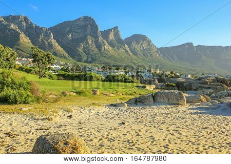 White long and spectacular beach of Camps Bay with Table Mountain National Park behind him. Camps Bay is one of the most exclusive resort of South Africa Also known as Cape Town's Riviera.