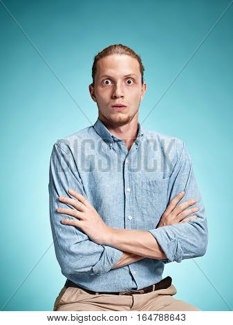 The surprised young man in blue shirt standing over blue studio background