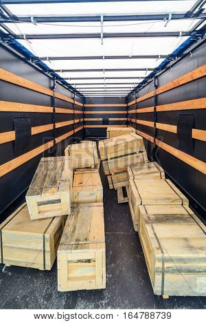 Several wooden crates inside the cargo semitrailer. The boxes piled in a disorderly pile. Interior view of empty semi truck lorry