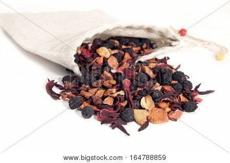 fruits and berries tea with hibiscus in linen bag over white