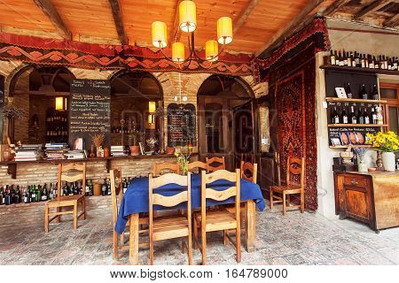 SIGNAGI, GEORGIA - OCT 7, 2016: Restaurant's interior in the Georgian style with wine bottles on shelves and carpets on walls on October 7, 2016. Signagi of Kakhetia has a population 2.200