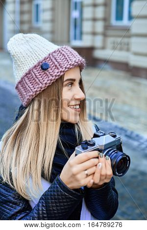 Beautiful girl photographer photographing the old town with retro camera. She is wearing a knitted cap