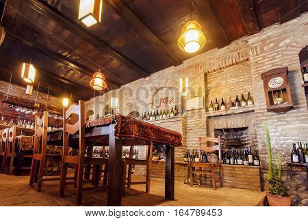 SIGNAGI, GEORGIA - OCT 7, 2016: Brick walls of old restaurant with wine bottles on shelves wooden tables and bright lamps on October 7, 2016. Signagi of Kakhetia has a population 2.200