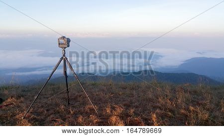 photo camera mounted on tripod outdoors  in nature background